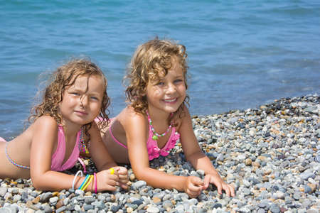 two pretty little girls lying on stony beach near sea photo