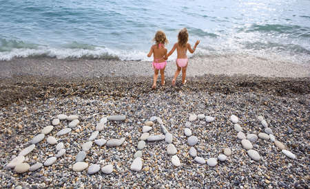 Inscription from stones BEACH at stony coast, two pretty little girls on seacoast photo