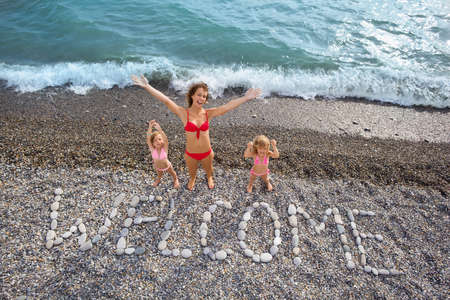 lifted hands: Inscription from stones WELCOME at stony coast, young woman and two little girls  lifted hands upwards on seacoast Stock Photo
