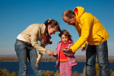 Little girl plays with parents nature in bright autumn day. photo