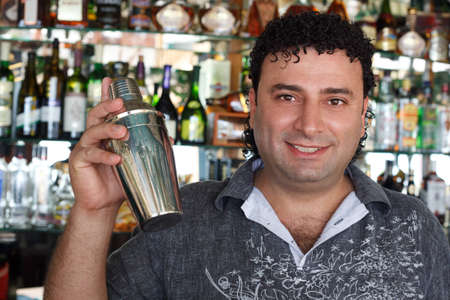 Barman with shaker behind bar rack. Smiling man against shelves with bottles. photo