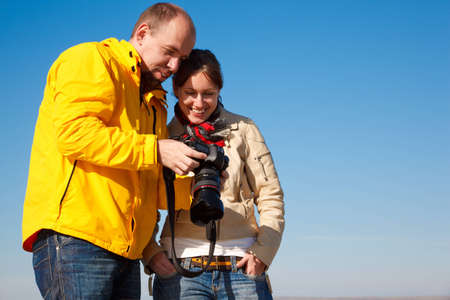 Photographer shows  camera shot girl. Pair of autumn clothing against sky. photo