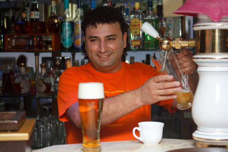 Bartender fills glass of beer. Smiling man against shelves with bottles. photo