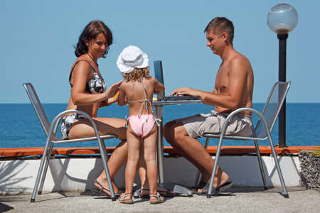 Family of three people resting on sea. On warm sunny day they sit outdoors at a table with laptop. photo