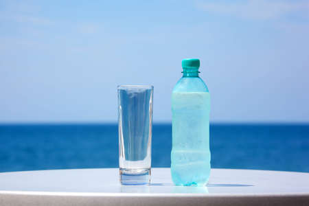 Bottle of water and glass on table under open sky on background of sea. Stock Photo - 11373981