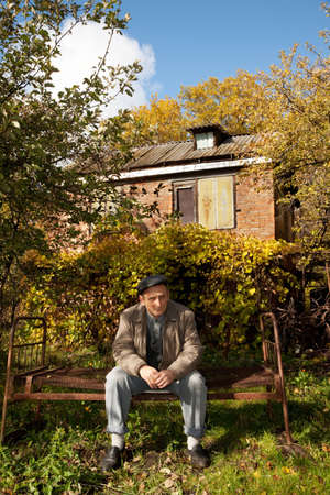 pensionary: Serious middleaged man sit on old rusty bed in autumnal garden Stock Photo