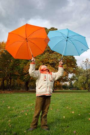 autumn colour: Boy in autumn park. Holds over head two colour umbrellas under cloudy sky.