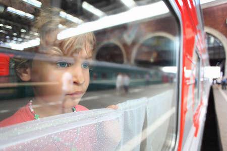 railway transport: little girl look from train window Stock Photo