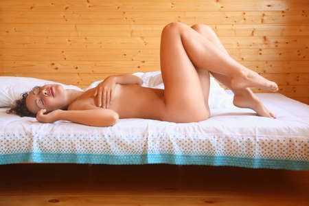 naked beautiful hot woman lying on bed in cosy wooden room, closed eyes     Stock Photo - 11396093