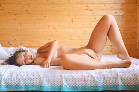 naked: naked beautiful hot woman lying on bed in cosy wooden room, Lying on back