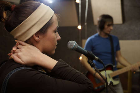 vocalist: vocalist girl is singing. electro guitar player in out of focus Stock Photo