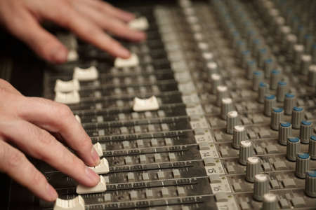 analogs: sound producer moving faders of dirty sound mixer pult. focus on fingers of right hand