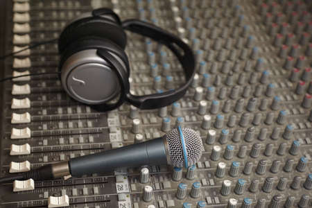 micro recording: headphones and microphone on old dirty sound mixer pult. microphone in focus Stock Photo