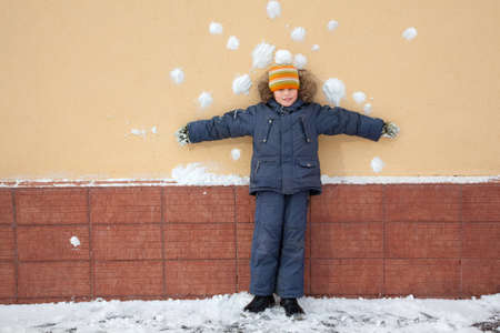 bombardment: boy kid is standing near wall with snowballs snow stains. Risky bombardment shooting of defenceless boy by snowballs near wall  Stock Photo