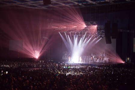 muzikale prestaties concert. lichtshow. groep band zanger is het uitvoeren van dansen op het podium. heldere lichten boven het podium
