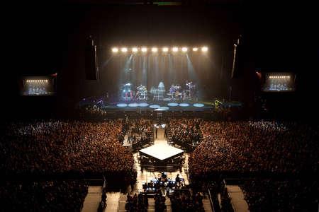 muzikale prestaties concert. illumnation lichtshow. groep band zanger voert dansen op het podium. heldere lichten boven het podium