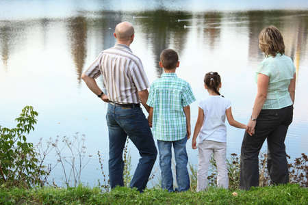 hands behind back: family with two children in early fall park near pond. they are looking at water.