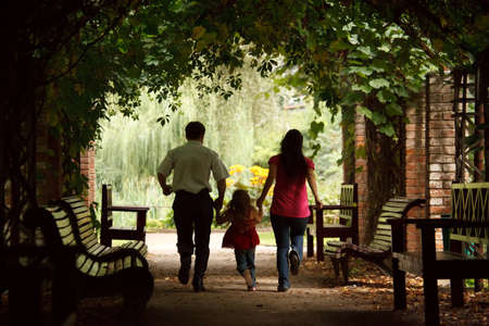 avenues: Parents together with daughter escape on tunnel from ivy in summer garden. Stock Photo