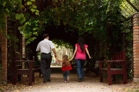 Parents together with daughter enter into tunnel from an ivy in summer garden. photo