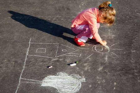 girl draws painting line a chalk on asphalt. photo