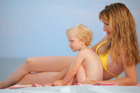 denuded: beautiful woman with blond  little baby girl lying on beach, looking afar