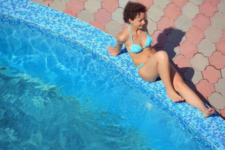 beautiful sexual woman sitting near pool on resort, relaxing on ledge pool