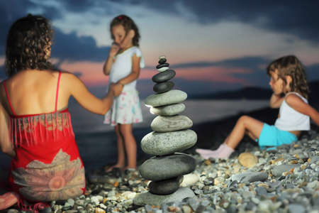 mothers group: two little girls and beautiful woman in red sundress sitting near to pyramid from pebble on stone seacoast in evening
