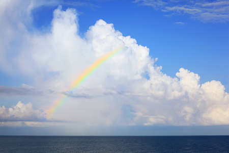 horizon over water: white big clouds and multi-coloured  rainbow over sea in afternoon