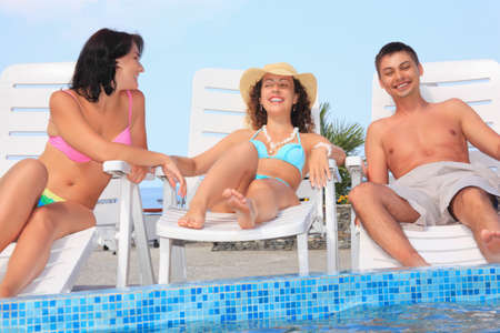 lounges: Smiling man and two young women reclining on chaise lounges near pool open-air Stock Photo