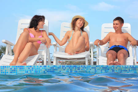 lounges: Smiling man and two young women reclining on chaise lounges near pool open-air,Talk with each other