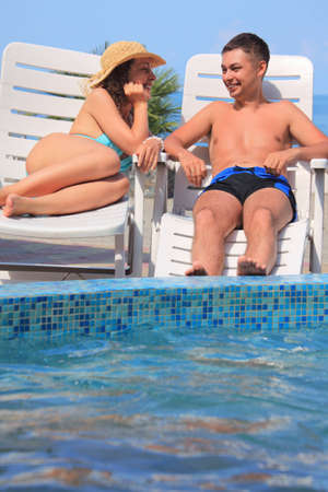 Young smiling woman and man reclining on chaise lounges near pool open-air photo
