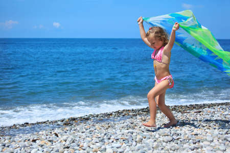 pretty little girl with fabric on stony seacoast, lifted hands upwards