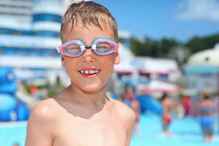 boy in watersport goggles near pool in aquapark of an entertaining complex photo