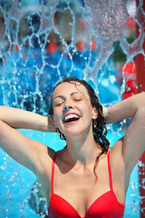 Smiling beautiful woman bathes in pool under water splashes, holding hands behind head Stock Photo - 11374490