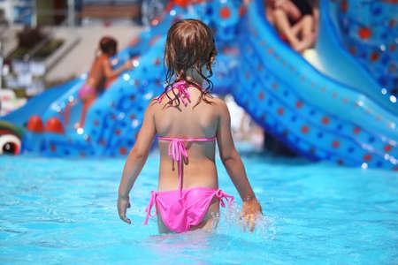 aquapark: little girl standing in pool in aquapark, standing back