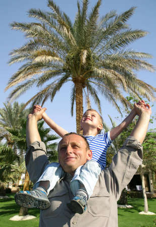 senior with child on shoulders in front of palm tree collage photo