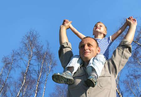 senior avec l'enfant sur les épaules en face de collage de printemps bouleau