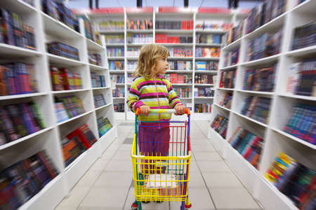 literacy: Little girl in bookshop, with cart for goods. There is one among racks.