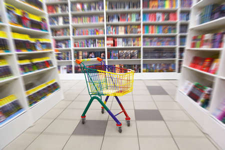 Bookshop interior. Before racks with books there is bright cart for purchases. Blurred. Stock Photo - 11574876