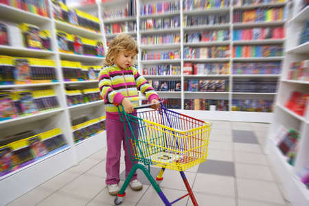 sceptic: Little girl in bookshop, with cart for purchases. Disapprovingly looks at book at itself in hands. Stock Photo