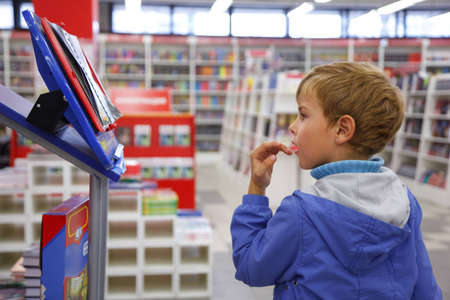 Bookshop, boy in blue jacket with surprise looks at show-window. Imagens