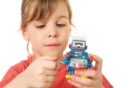 pretty little girl in red T-shirt plays with clockwork robot isolated on white background photo