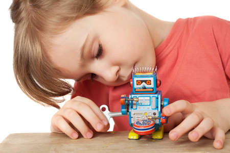 little girl in red T-shirt plays with clockwork robot isolated on white background photo