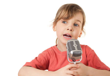 pretty little girl in red T-shirt sing in old style microphone isolated on white background, looking aside photo