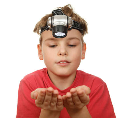 Portrait of boy with flashlight on his head on white background. Smiling, he looks at his hands. photo