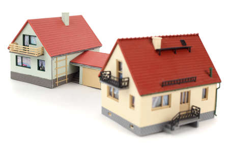Models of two houses with garage for car on white background. Focus on the distant house. photo