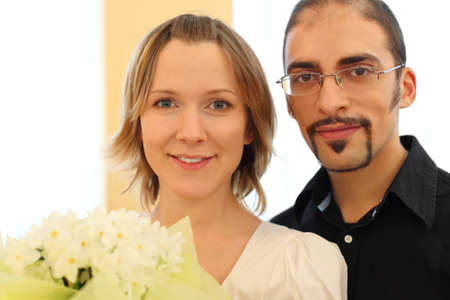 portrait of man in glasses and beauty blond girl with flowers bouquet, looking at camera photo