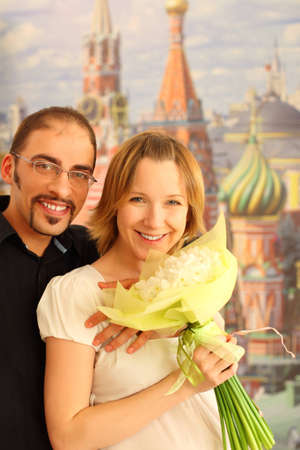 man in glasses embracing beauty blond girl with flowers bouquet, looking at camera and smiling, Moscow Kremlin on background photo