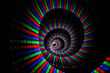 Luminous colors of rainbow trail in form of spiral on black background. Isolated. photo