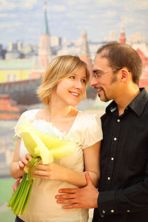 man in glasses embracing beauty blond girl with flowers bouquet, looking to each other and smiling photo